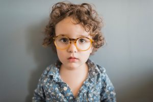 Young child with worried expression and glasses